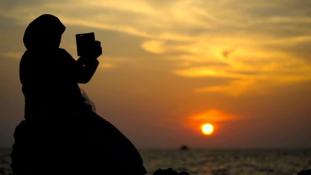 vídeos y material grabado en eventos de stock de silueta turismo de mujer muslimah sms en smartphone. - guionista