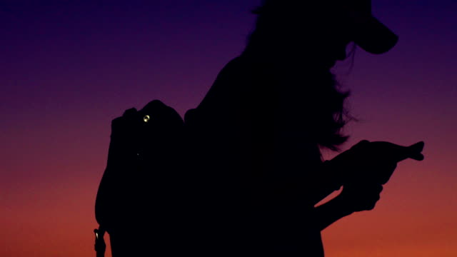 Silhouette Of A Backpacker With Smart Phone at sunset