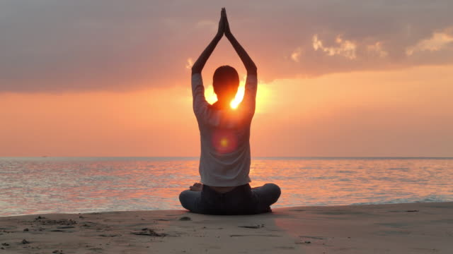 silhouette of a beautiful yoga woman on a beach.she is performing yoga in front of beautiful sea on sunset day.people,vacation,healthy,travel,lifestyle,leadership.vacations - istock - buddhism stock videos & royalty-free footage