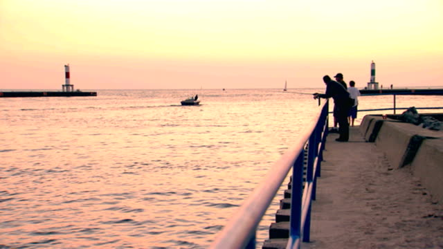 vidéos et rushes de silhouette of a boat leaving the channel and people standing on the pier at sunset  - aller tranquillement