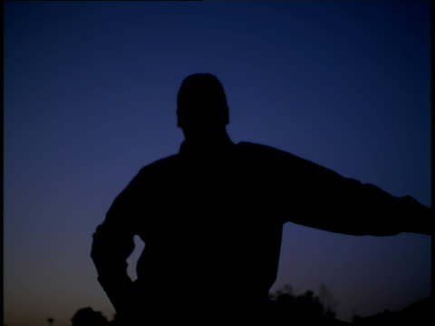 vídeos de stock e filmes b-roll de silhouette of a business man outdoors after dusk - só um homem maduro