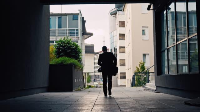 vidéos et rushes de slo mo silhouette d'un homme d'affaires sortant du passage inférieur - un seul homme