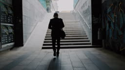 SLO MO Silhouette of a businessman walking out of underpass