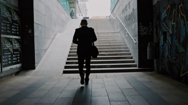 slo mo silhouette of a businessman walking out of underpass - in silhouette stock videos & royalty-free footage