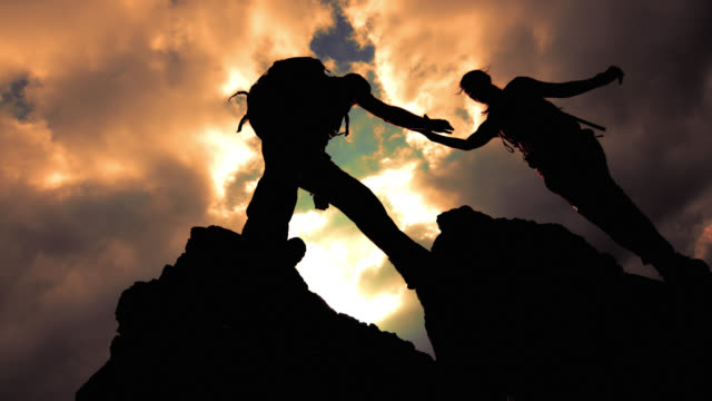 slo mo silhouette of a couple reaching the top together - a helping hand stock videos & royalty-free footage