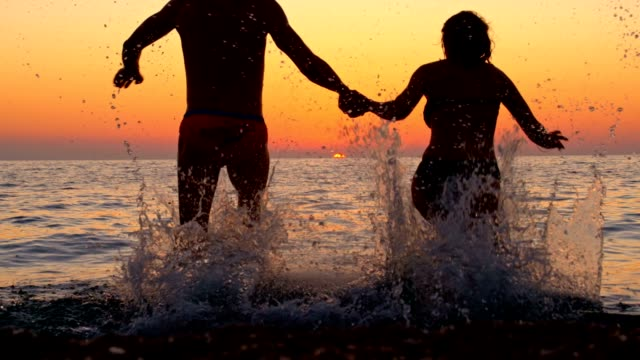 SLO MO Silhouette of a couple running into the sea