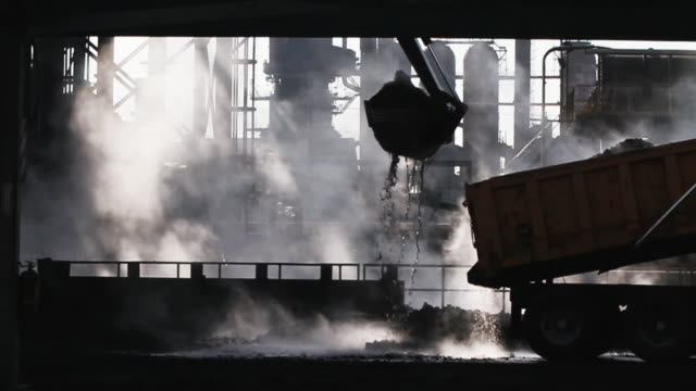 Silhouette of a crane dumbing metallurgical coke with steam rising