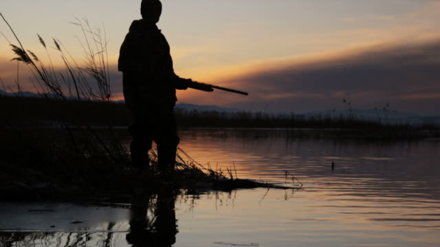 silhouette of a duck hunter standing on the lake