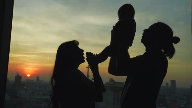 vídeos de stock e filmes b-roll de a silhouette of a family with a baby and parents caring for them shoots like black silhouettes in the evening. where the sun is setting - família jovem