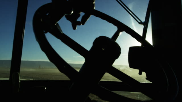 silhouette of a farmer's hand steering a tractor's steering wheel from inside of a tractor cab as he navigates through a corn field - agricultural equipment stock videos and b-roll footage