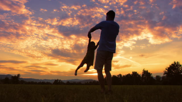 SLO MO DS Silhouette of a father spinning his daughter around in meadow at sunset