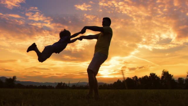 slo mo ds silhouette of a father spinning his son around outside at sunset - mid adult stock videos & royalty-free footage