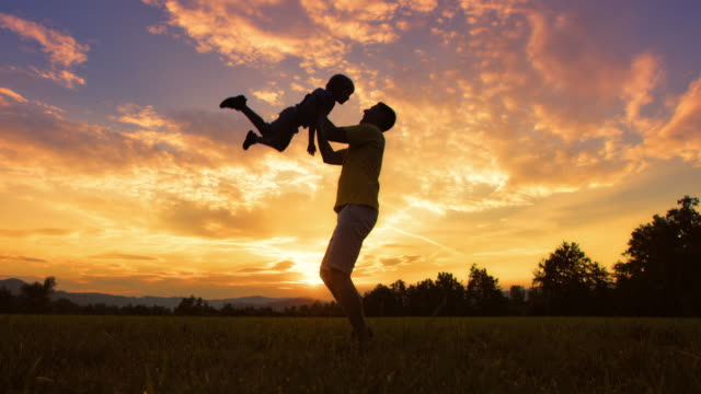 SLO MO DS Silhouette of a father tossing his son into air outside at sunset