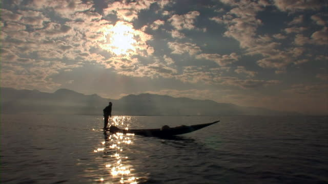Silhouette of a fisherman rowing a boat