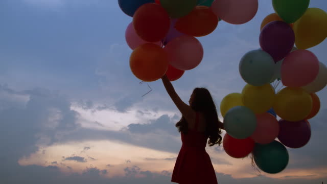vídeos de stock e filmes b-roll de silhouette of a flying young girl with a balloon against a background of a blue sky with clouds at sunset. - formal