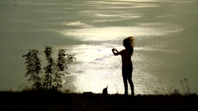 シルエットの女性は海に沈む夕日 - 美術工芸品点の映像素材/bロール