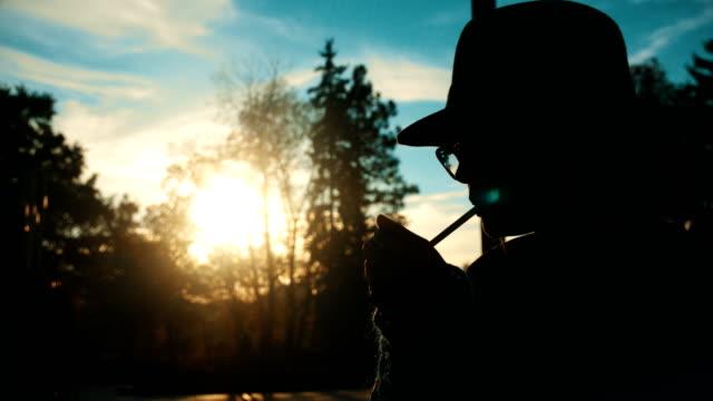 照明と日没のスローモーションでタバコを吸う女の子のシルエット ショット - 横顔点の映像素材/bロール