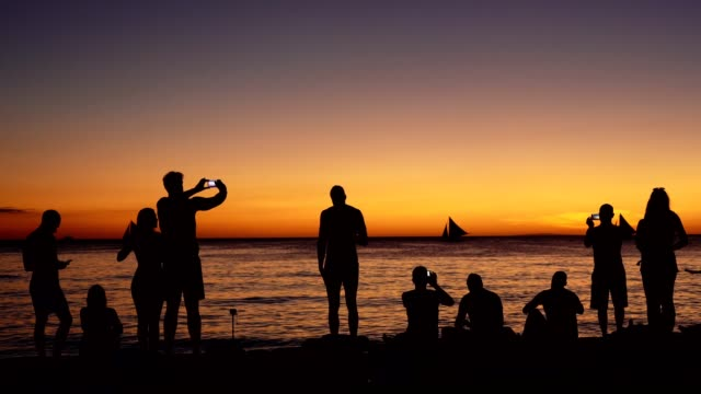 silhouette of a group of friends having fun on the beach - isole del pacifico video stock e b–roll