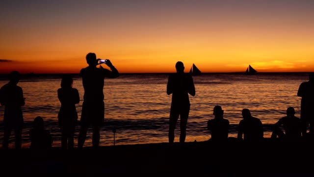Silhouette of a group of friends having fun on the beach