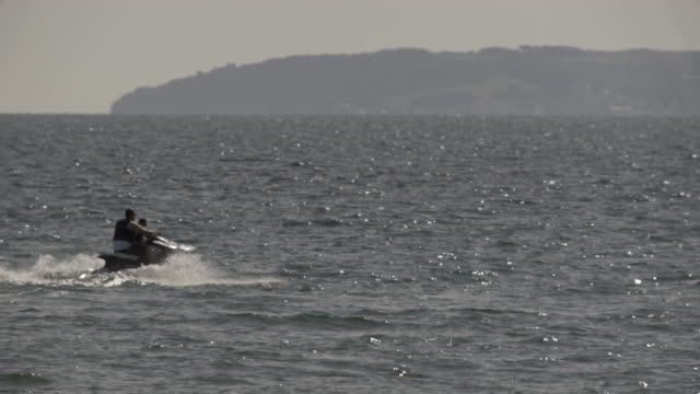 silhouette of a jet ski in the open sea. - bournemouth england stock videos & royalty-free footage