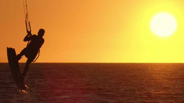 slo mo silhouette of a kitesurfer performing a jump - kiteboarding stock videos & royalty-free footage
