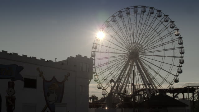 silhouette of a large ferris wheel at on the jersey shore with the sun setting behind.  the location is ocean city nj at gillian's wonderland pier. - 遊歩道点の映像素材/bロール