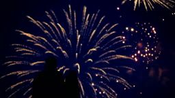 Silhouette of a loving couple of people looking at the fireworks.