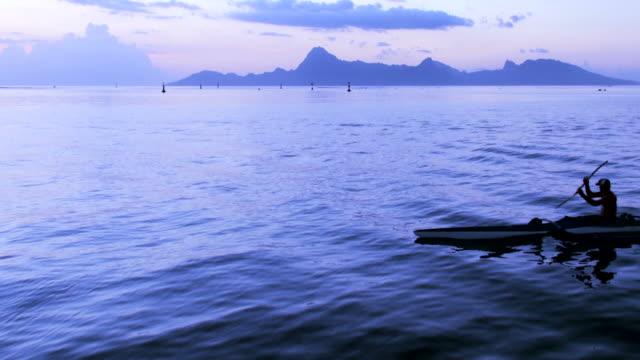 silhouette di un uomo in canoa subito dopo il tramonto - kayak video stock e b–roll