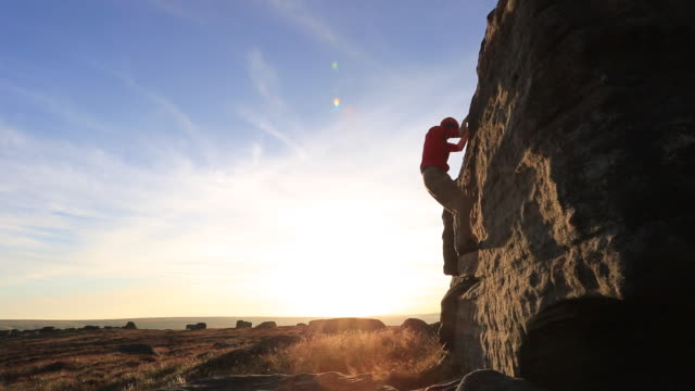 silhouette of a man climbing boulders while bouldering. - top garment stock videos and b-roll footage