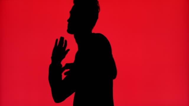 stockvideo's en b-roll-footage met silhouet van een mens die alleen op een rode achtergrond danst - dance studio
