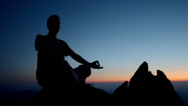 stockvideo's en b-roll-footage met hd dolly: silhouette of a man meditating - bergrug