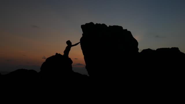 Silhouette eines Mannes auf den Felsen bei Sonnenuntergang