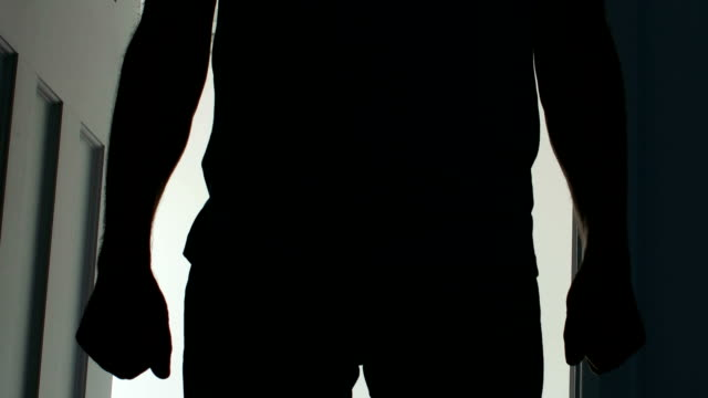 silhouette of a man opening a door and entering a dark room. - stand stock videos & royalty-free footage