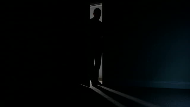 Silhouette of a man opening a door to dark room.