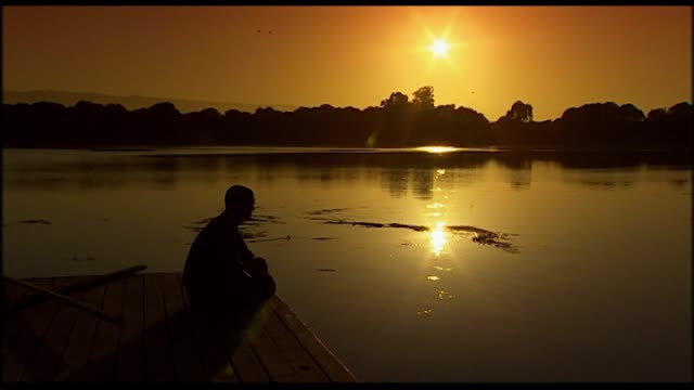 silhouette of a man sitting by a lake at sunset - life balance stock videos & royalty-free footage