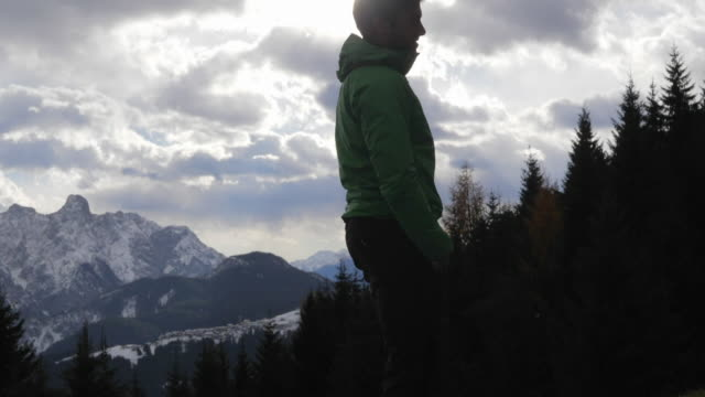 silhouette of a man standing and looking at the scenic view of clouds and mountains in the winter. - weitwinkelaufnahme stock-videos und b-roll-filmmaterial