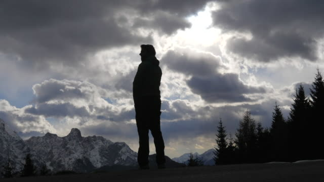 silhouette of a man standing and looking at the scenic view of clouds and mountains in the winter. - slow motion - caucasico video stock e b–roll
