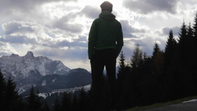 vídeos y material grabado en eventos de stock de silhouette of a man standing and looking at the scenic view of clouds and mountains in the winter. - slow motion - abrigo de invierno