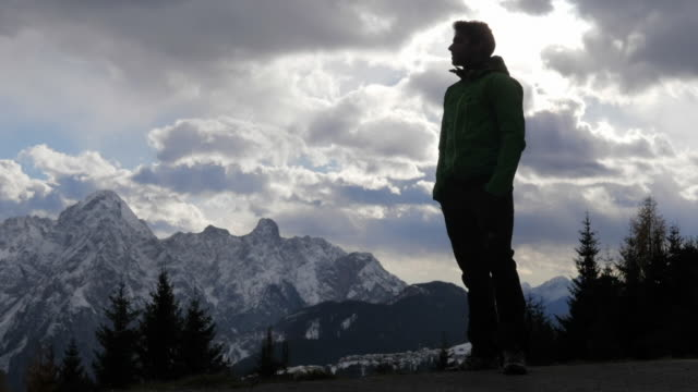 Silhouette of a man standing and looking at the scenic view of clouds and mountains in the winter. - Slow Motion