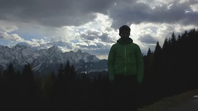 silhouette of a man standing and looking at the scenic view of clouds and mountains in the winter. - slow motion - weitwinkelaufnahme stock-videos und b-roll-filmmaterial