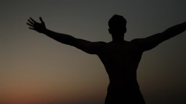 vidéos et rushes de silhouette of a man stretching his body  - musclé