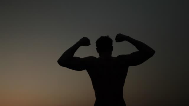 vídeos y material grabado en eventos de stock de silhouette of a man stretching his body  - manos detrás de la cabeza