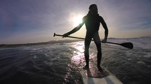stockvideo's en b-roll-footage met silhouette of a man sup stand up paddleboard surfing on a wave. - slow motion - houding begrippen