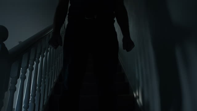 Silhouette of a man walking down a dark stairway.