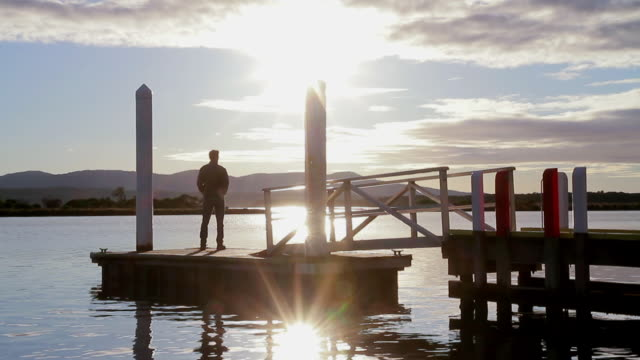 ws silhouette of a man walking onto small jetty / mallacoota, victoria, australia - jetty stock videos & royalty-free footage