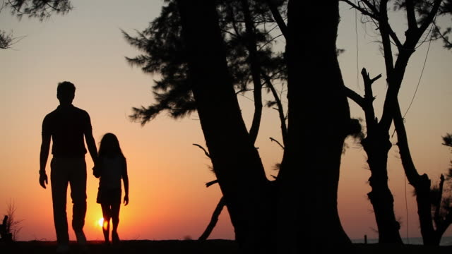 Silhouette of a man walking with his daughter at sunset