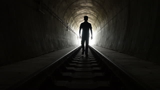 silhouette of a men walking in train tunnel. - railroad track stock videos & royalty-free footage