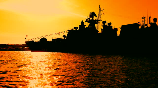 silhouette of a modern warship at sunset - warship stock videos & royalty-free footage
