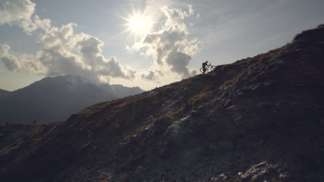 Silhouette of a mountain biker hiking up hill on a trail in the mountains. - Slow Motion