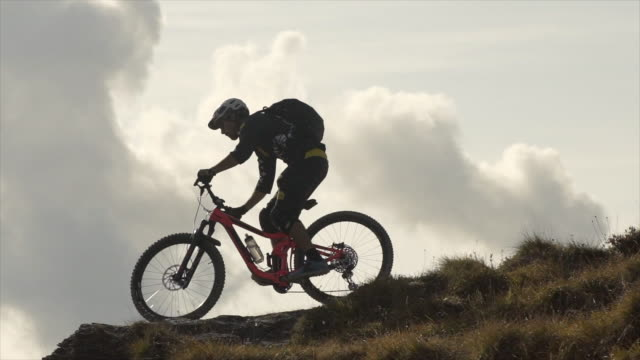 Silhouette of a mountain biker riding downhill on a trail in the mountains. - Slow Motion